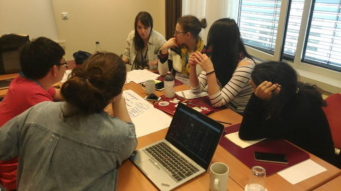Students sit round a table in a small room concentrating on a problem.