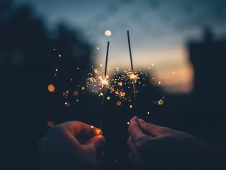 Two hands, sparklers at dusk