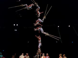Circus acrobats balance on each other while juggling