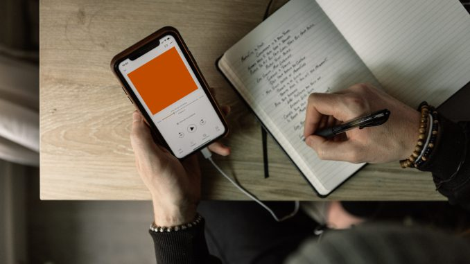 One hand holds a phone playing a recording through headphones. The other hand writes in a notebook