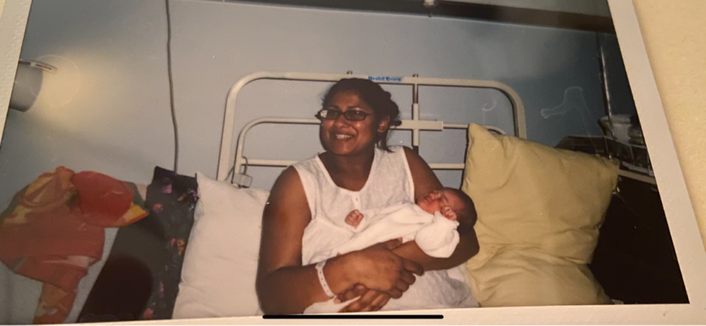 A photograph of Sarah Guerra (the author) smiling with her daughter Kaela, who is one day old, in a hospital bed.
