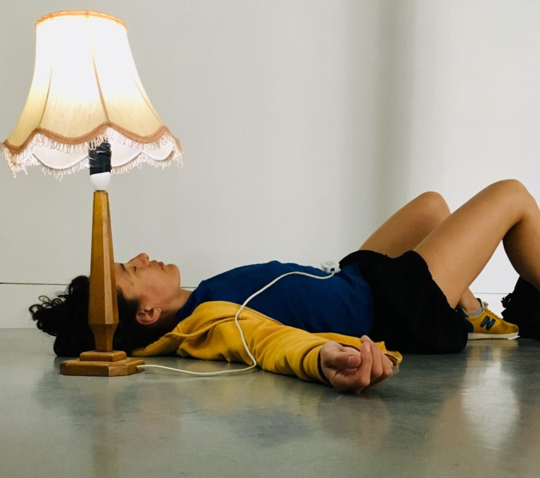 A woman laying on her back on the floor next to a lamp.