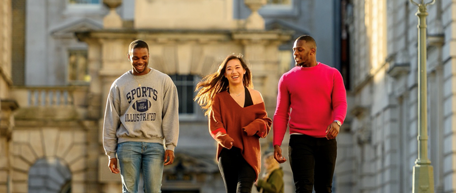 3 King's students walking across the quad at Strand Campus