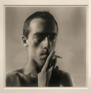 A black and white portrait photograph of David Wojnarowicz drawing on a cigarette looking at the camera