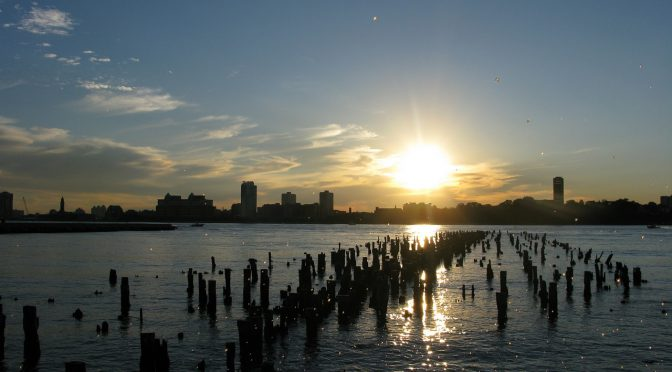 A photo of a low sun in a blue sky with the light glinting across the New York skyline onto the ruins of Chelsea Pier