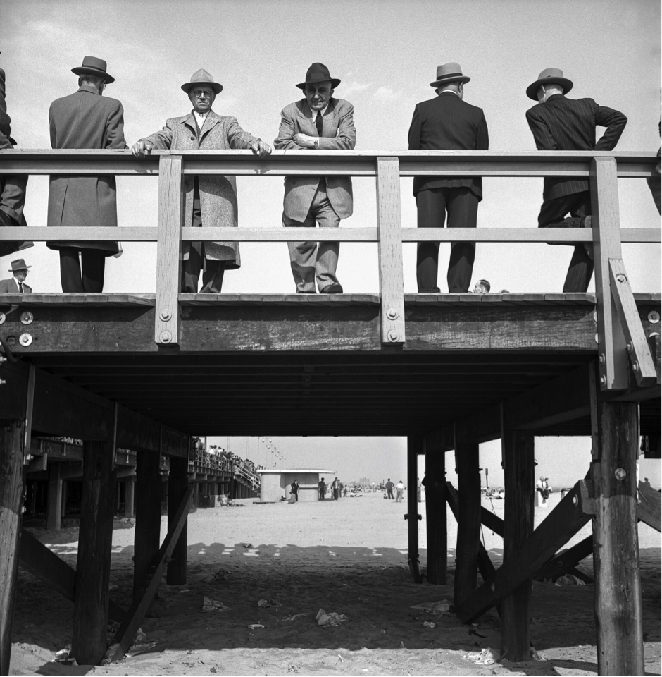 Black and white image of men standing on a small pier wearing coats and hats