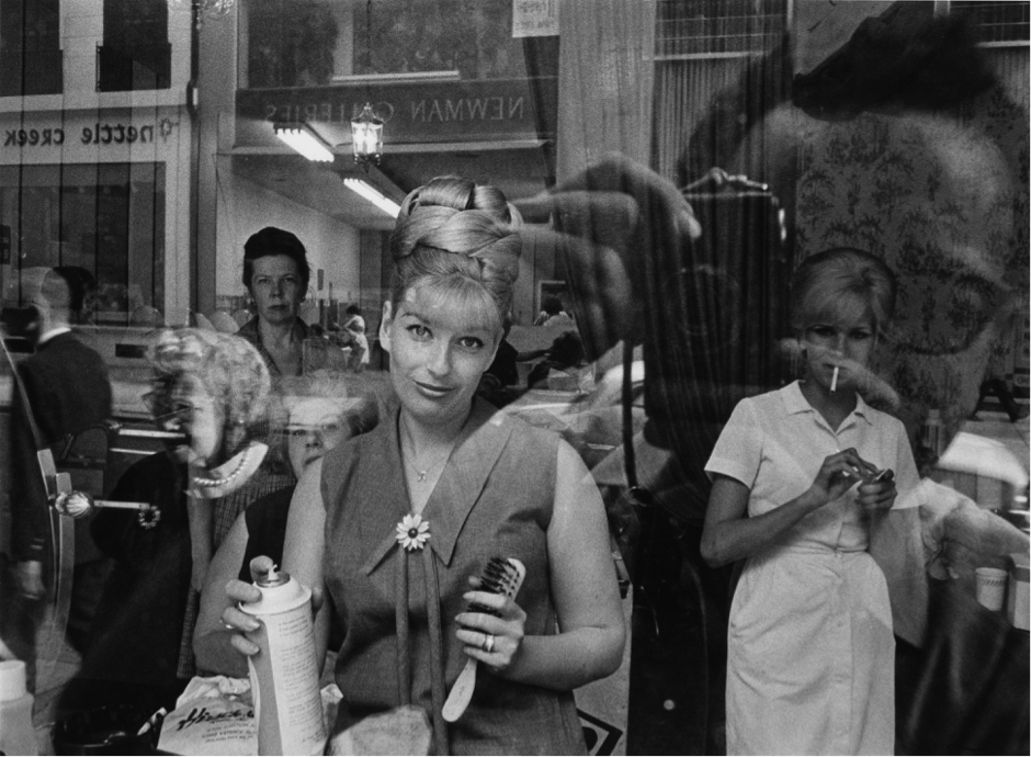 A black and white photograph of a woman looking out at the camera through the front window of a hair salon