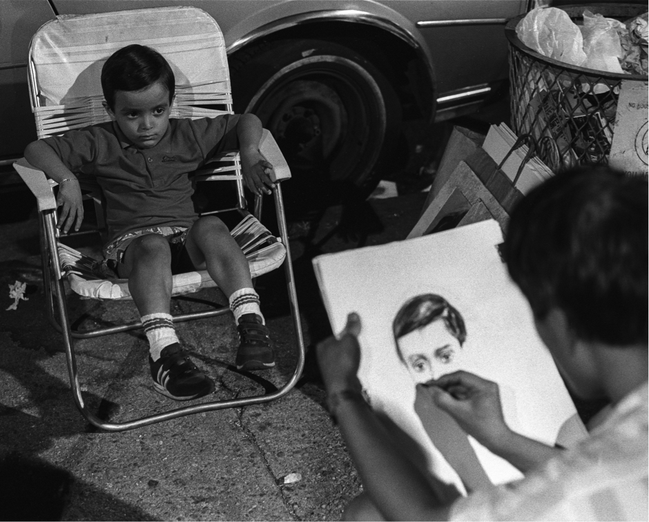 A photograph of a young boy swamped in an fold up chair getting his portrait done