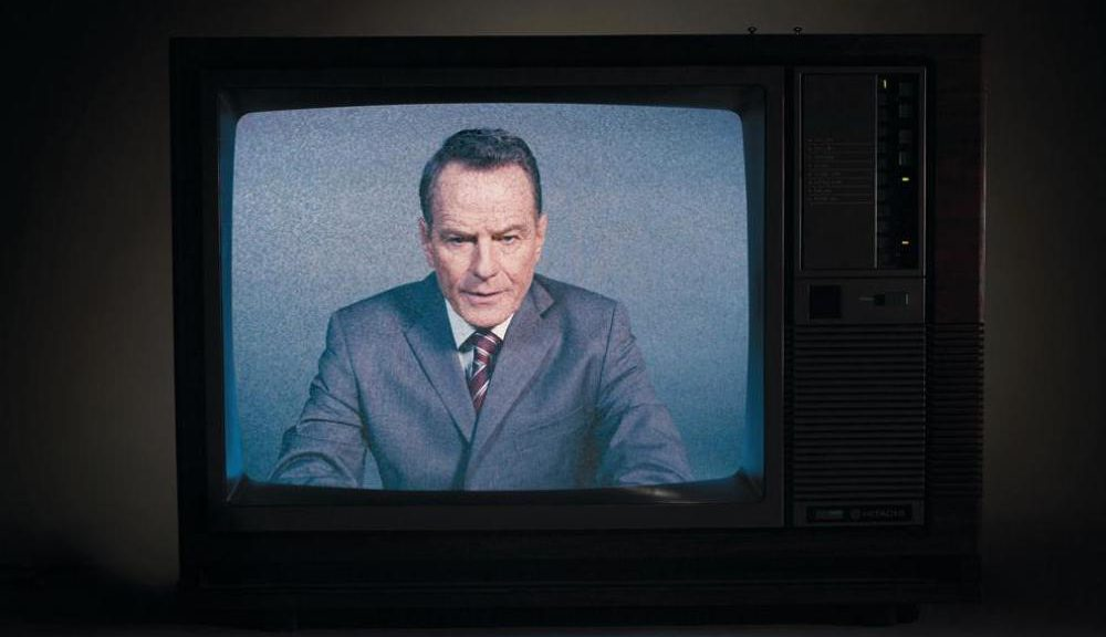 Bryan Cranston in a suit on a fuzzy retro TV screen looking serious