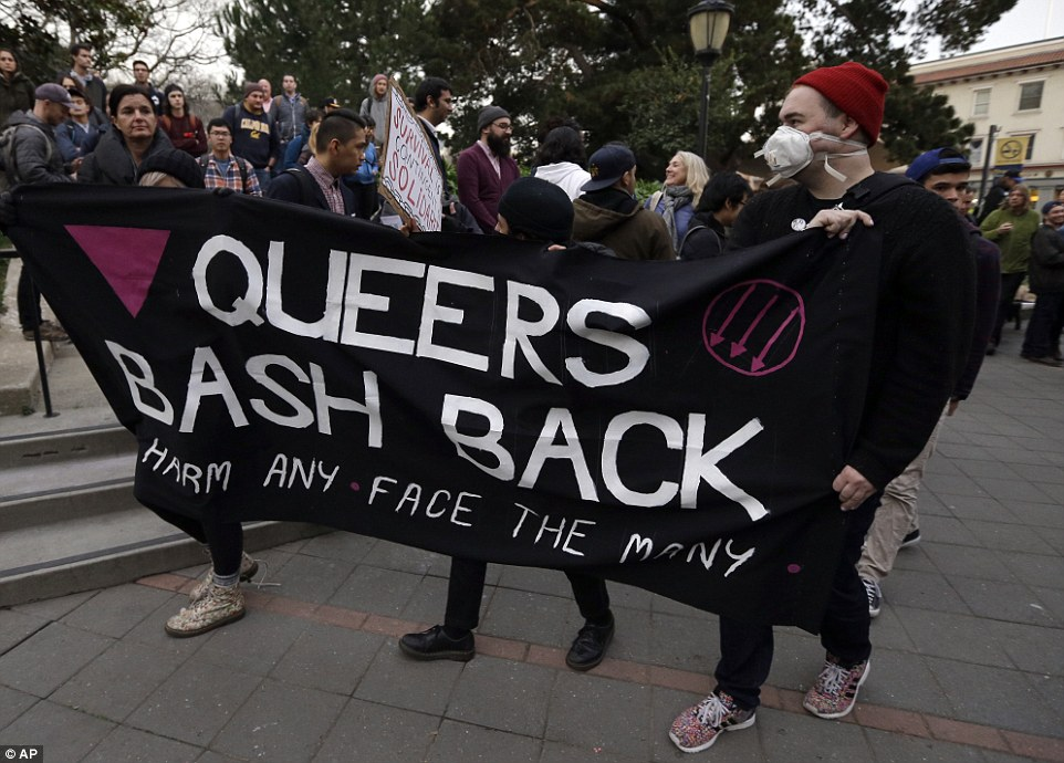 Image via AP: Two protesters wearing black carry a black banner emblazoned with 'Queers Bash Back: Bash Any Face the Many'