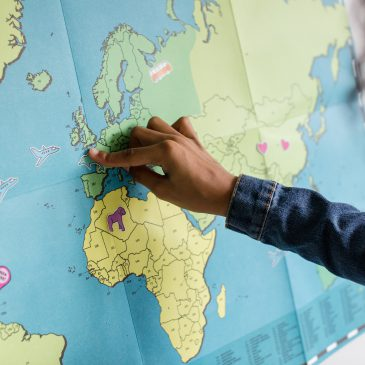 person putting a pin on a world map