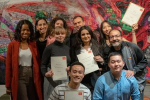 Ten people holding certificates and smiling at the camera