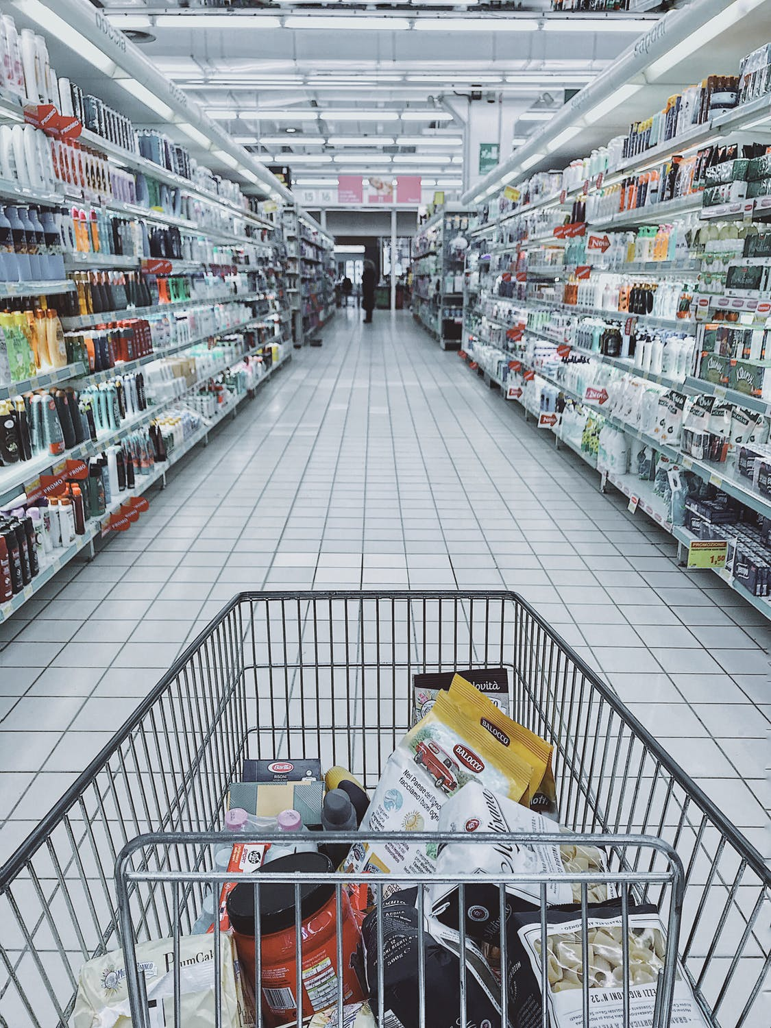 perspective of a person with a shopping cart, looking at an array of items in the shelves of a shop