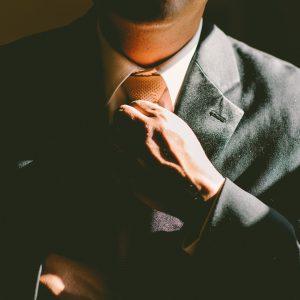 person tying a tie in businesswear