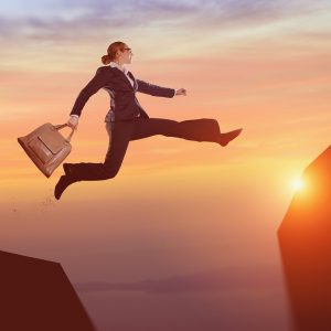 Image of a woman leapingon top of a mountain during sunrise