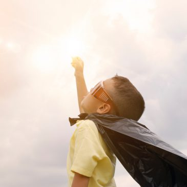 Boy wearing a cape and celebrating