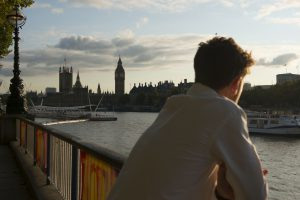 A close up photograph of a man's back as he looks at the British Houses of Parliament across the River Thames.
