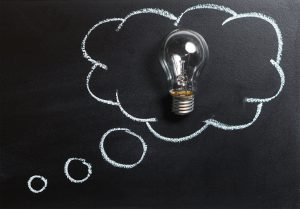 chalkboard drawing of a thought bubble with a real lightbulb within it