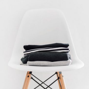 Black and grey clothes piled neatly on white chair against white background