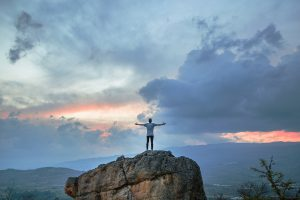 Man standing on top of a rock during sunrise