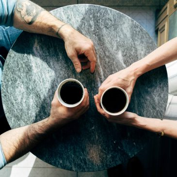 Ariel shot of a man and a woman holding two cups of coffee on a round coffee table.