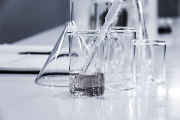 Close up of glass beakers sitting on a white desk