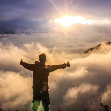 Image of a figure standing on top of a mountain during sunrise