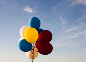 different coloured balloons against a blue sky