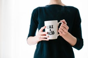 "Image of a woman holding a mug that reads ""like a boss"""