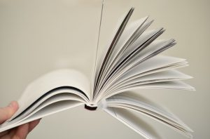 A notebook opened with pages flipping, being held in the air