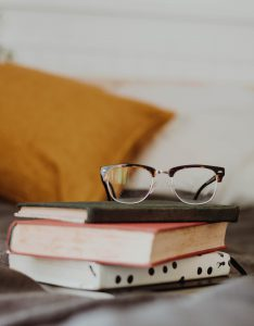 Image of glasses on top of a pile of books