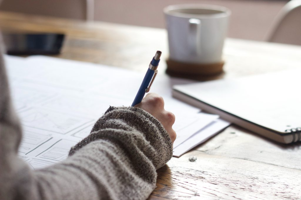 Person with pen in hand making notes