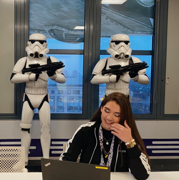 Image of Fio at a desk with Star Wars Stormtroopers in the background