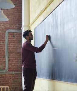 Image of man writing to chalkboard. Click here to read the blog