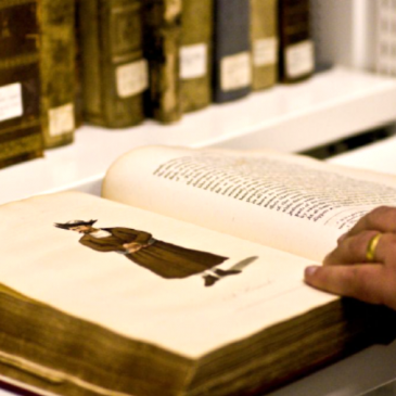 Image of hand resting on an old manuscript