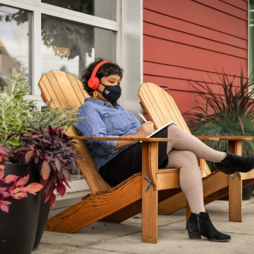 woman with facemask and headphones sitting on chair