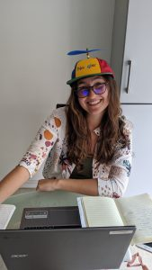 Nicole at her laptop, wearing a Google cap with a propeller on top
