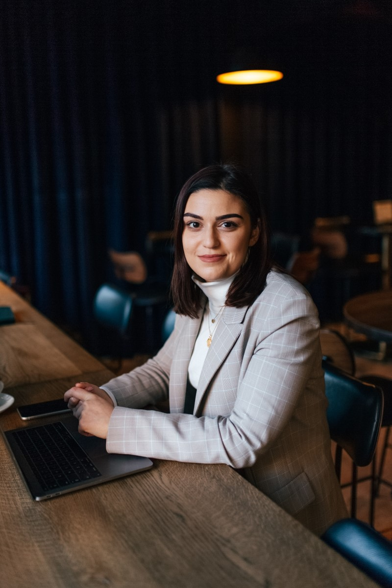 Joana smiling at a wooden desk with a laptop, and business blazer