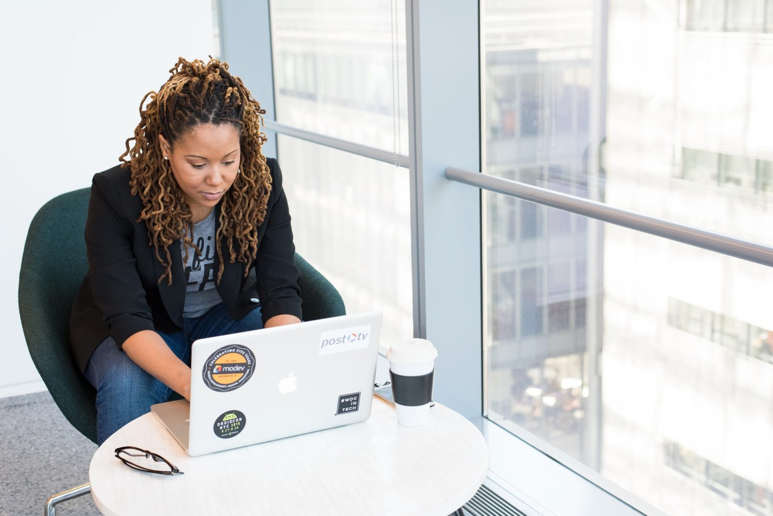 Image of black female employer using computer by a large window