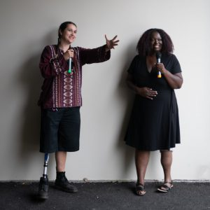 black woman and indigenous heritage woman speaking at an event