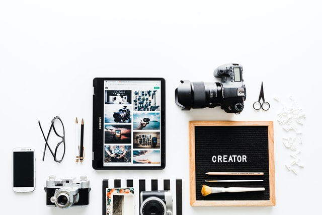 items on a white table including camera, notebook, phone and sign that says 'creator'