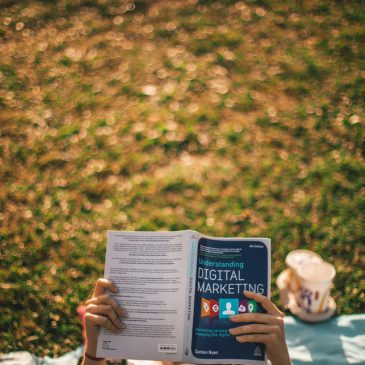 person lying on grass reading book, which is titled 'digital marketing'