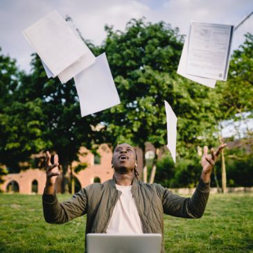 Man throwing various papers up into the air, while sitting by a laptop