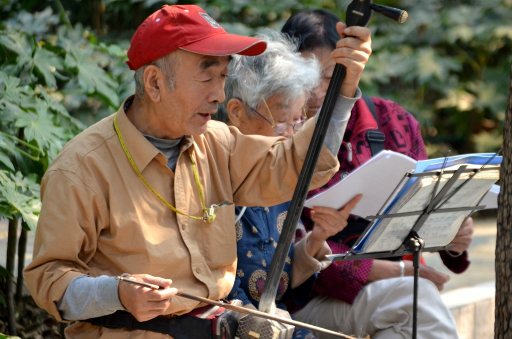 Chinese older people playing traditional music in urban park